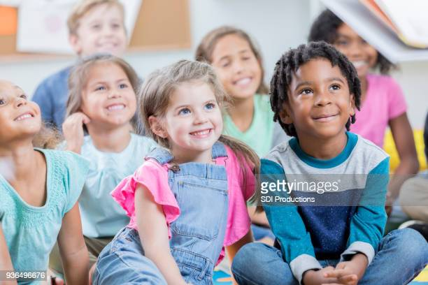 group of attentive school children during story time - elementary age stock pictures, royalty-free photos & images