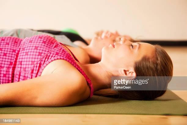 Grupo de atractiva joven Meditando y haciendo Yoga