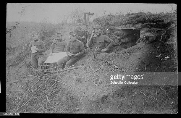 Group of Austrian soldiers in a First World War trench. One of the soldiers holds a field telephone.