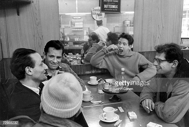 A group of avant garde American creative artists known in part as the Beats gather around a table at a restaurant they are painter and musician Larry...