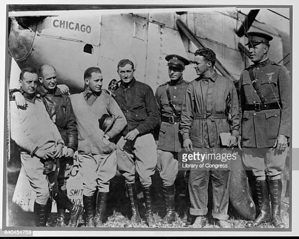 Group of aviators stand by a plane.