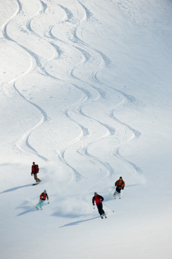 A group of backcountry skiers follow their guide down a slope in the Selkirk Mountains, Canada. - gettyimageskorea