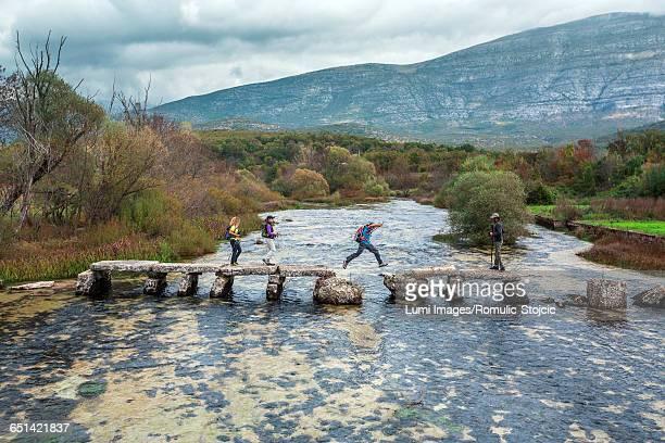 Group of backpackers crossing river through broken bridge