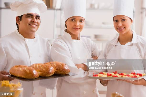 Group of bakers holding baked goods