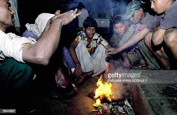 A group of Bangladeshi people attempt to keep warm by huddling around a fire of burning rubbish by a roadside in Dhaka 05 January 2004 According to...