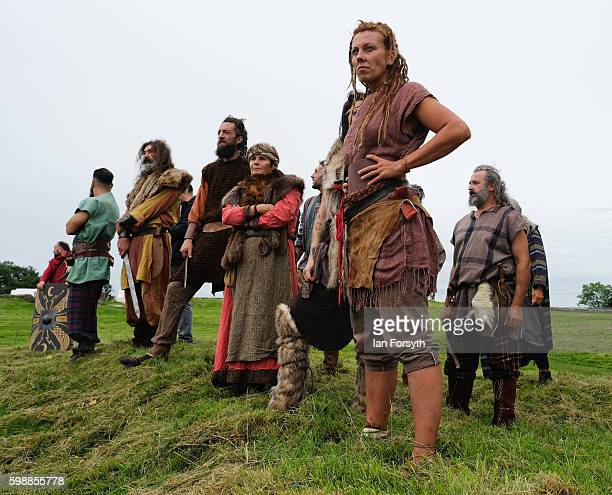 A group of Barbarian warriors stand on a small hill as the lives of Roman Legionnaires are reenacted during the Hadrian's Wall Live event at...