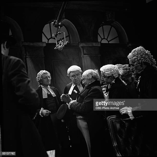 A group of barristers stand around a man in a tail coat in the 'The Trial of Mr Penwick' episode of the Alistair Cookehosted television anthology...
