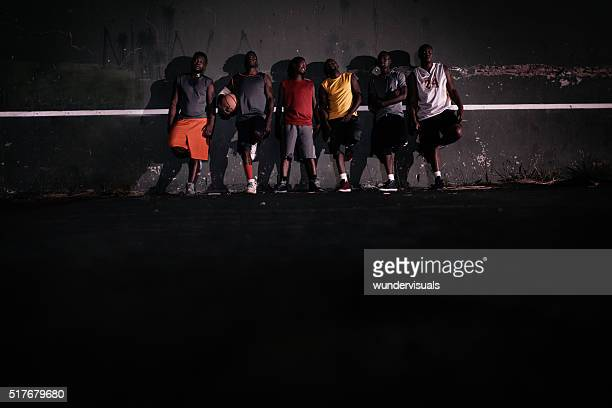 Group of Basketball Players Lined up Against Court Wall