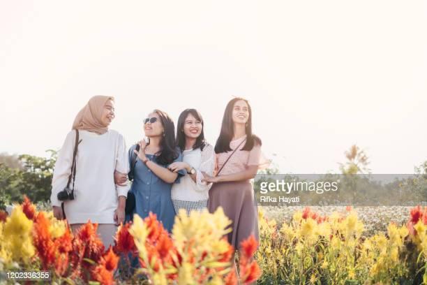 group of beautiful women at flower garden in yogyakarta - rifka hayati stock pictures, royalty-free photos & images