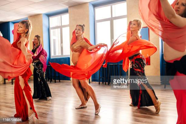 group of beautiful women on belly dance training - belly dancing stock photos and pictures