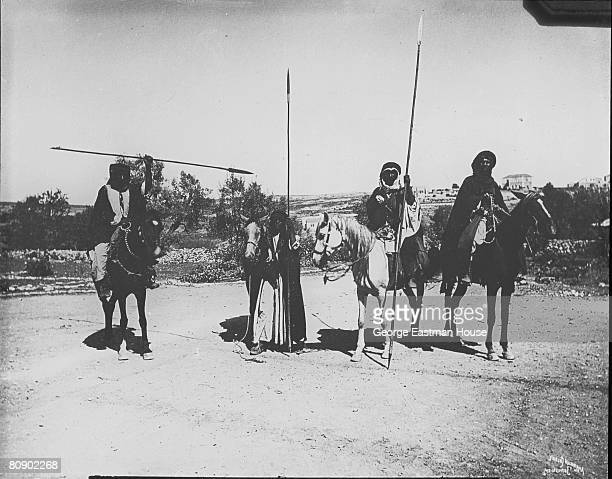 A group of Bedouin warriors on horseback brandish their spears
