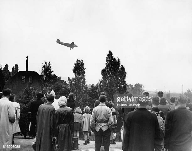 Group of Berliners by Tempelhof Airfield watches with anticipation as one of the United States C-47 Skytrain cargo planes descends from the sky...