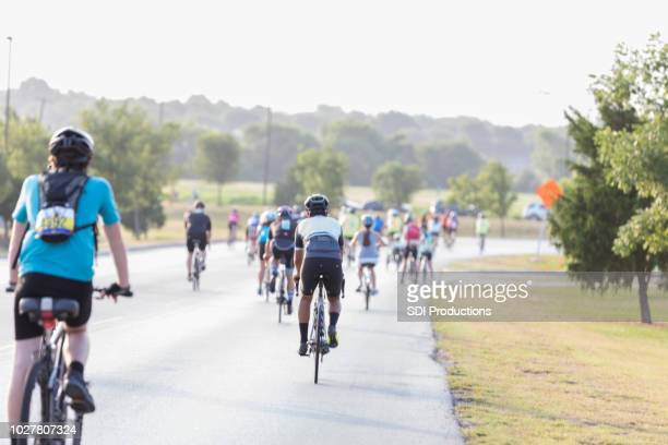 group of bike race for charity participants riding - charity benefit stock pictures, royalty-free photos & images