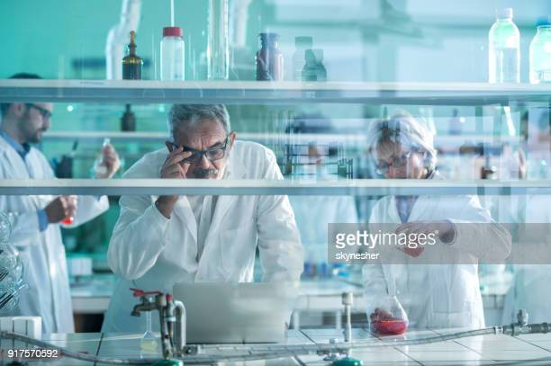 Gruppe von Biochemikern über neue Forschungen im Labor arbeiten.