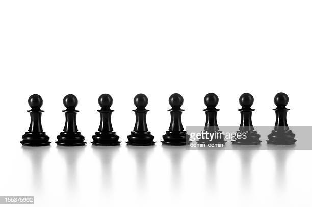 Group of black chess pawns in raw isolated on white