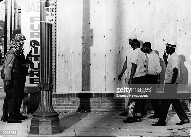 A group of Black men are confronted by state troopers with bayonets at a street corner in the Watts neighborhood Los Angeles California circa 1960s