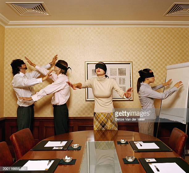 Group of blindfolded executives in conference room, arms outstretched