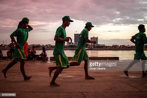 A group of boat oarsmen run before sunrise on the morning of the first day of the Water Festival on November 13 2016 in Phnom Penh Cambodia The...