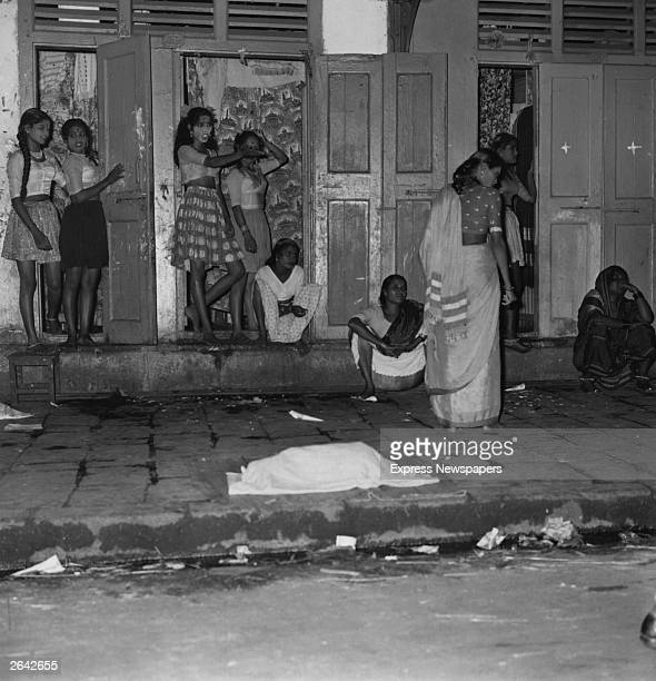 A group of Bombay prostitutes standing outside the 'cages' from which they work