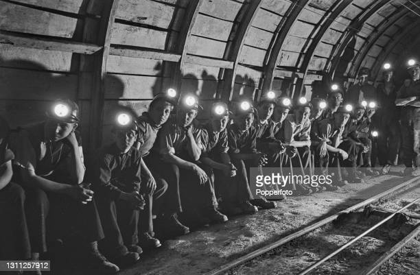 Group of boy coal-mining recruits, some as young as fourteen, await the arrival of a tram to take them to the coal face deep underground at Markham...