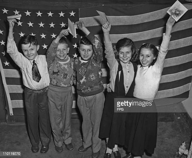 A group of boys and girls all displaced persons from Europe waving their invitations to a Thanksgiving party held at the Tavern on the Green Central...