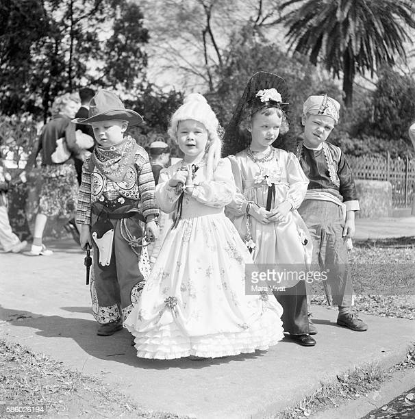 A group of boys and girls dressed up as pirates cowboys and princesses for Mardi Gras New Orleans Louisiana circa 1950
