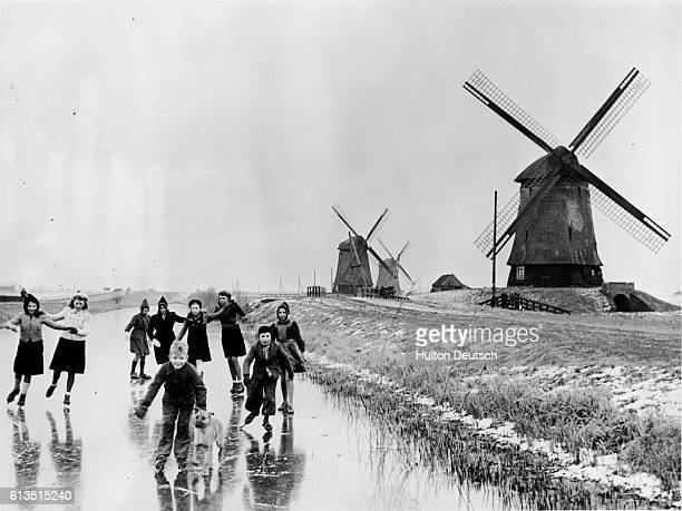 A group of boys and girls skates across the frozen surface of a canal at Vollendam in the Netherlands in January of 1946 | Location Vollendam...