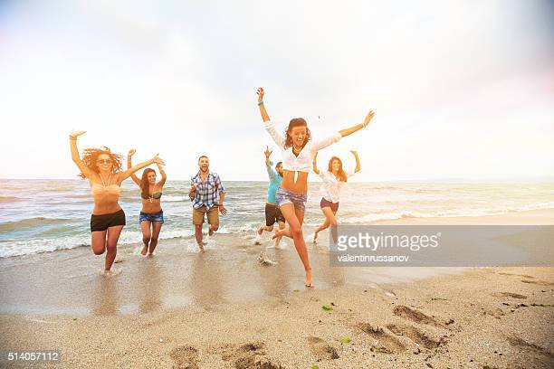 Group of boys ans girls running on the beach
