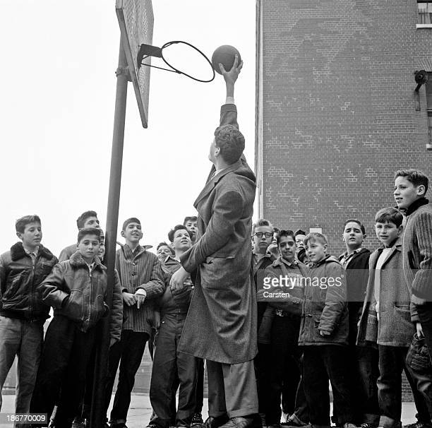 A group of boys are at a disadvantage playing basketball with Ed Carmel known as 'Big Ed' because of his giant proportions New York City circa 1955