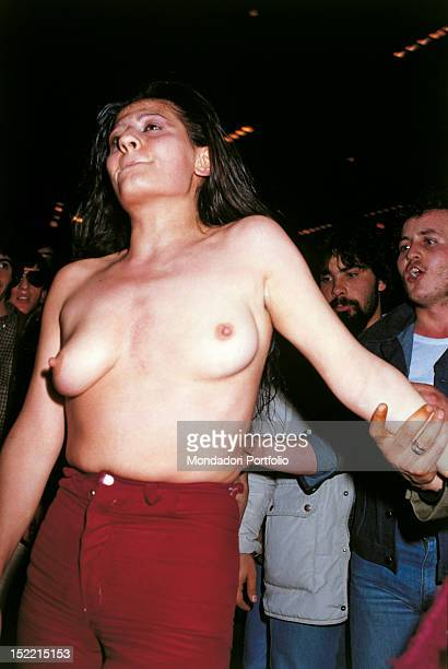 A group of boys are attracted by a woman who is dancing with bare breast on the dance floor of Studio 54 Milan 1979