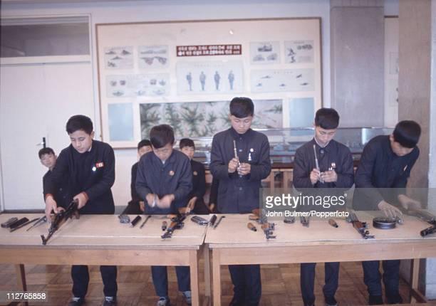 A group of boys assembling assault rifles North Korea February 1973
