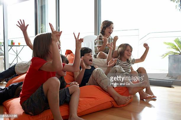 group of boys cheering in front of a television - children only stock pictures, royalty-free photos & images