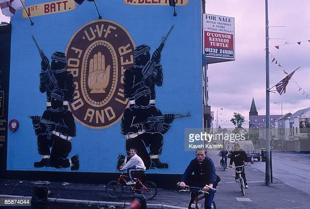 A group of boys cycle past a mural celebrating the loyalist paramilitary organization the Ulster Volunteer Force in the predominantly Protestant and...
