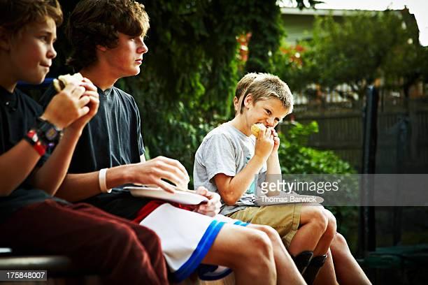 Group of boys eating on edge of halfpipe in yard