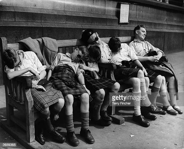 Group of boys, from the Glasgow School of Piping, fast asleep on a bench in Trafalgar Square, London.