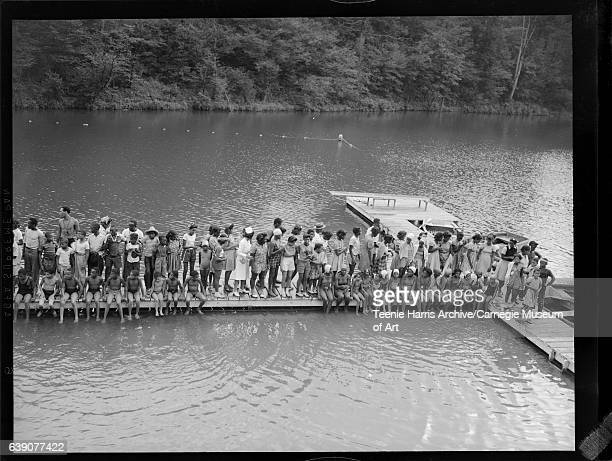 Group of boys girls men and women including nurse standing on wooden dock including group of boys on left and group of girls on right seated on dock...