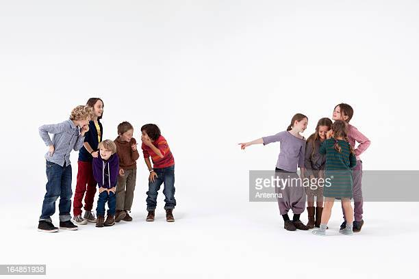 a group of boys laughing while a group of girls gossips about them - teasing stock pictures, royalty-free photos & images