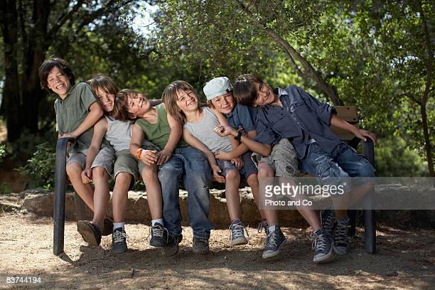groupe de garçons lean ensemble sur le banc - seulement des enfants photos et images de collection