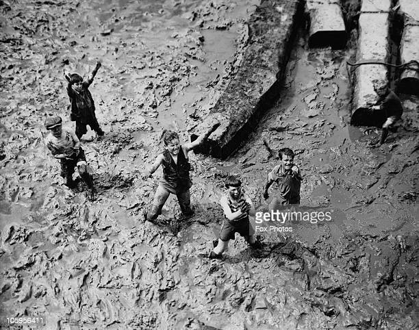 A group of boys looking for coppers thrown down by holidaymakers in the mud at low tide Portsmouth circa 1935