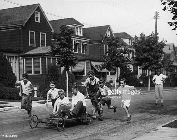 A group of boys on a residential street run after the gokart that two of them ride that they have put together from an old motorcycle and a homemade...