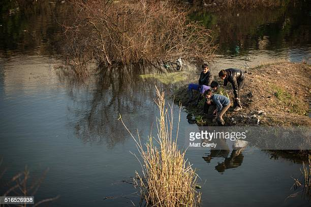 A group of boys play besides a lake of rainwater at the Idomeni refugee camp on the Greek Macedonia border on March 19 2016 in Idomeni Greece...