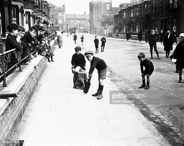A group of boys play cricket on a London street in 1927