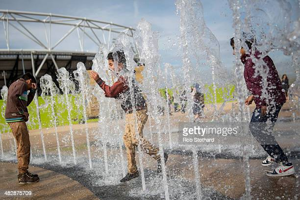 A group of boys play in fountains in front of the Olympic Stadium at the Olympic Park on April 5 2014 in London England The Queen Elizabeth Olympic...
