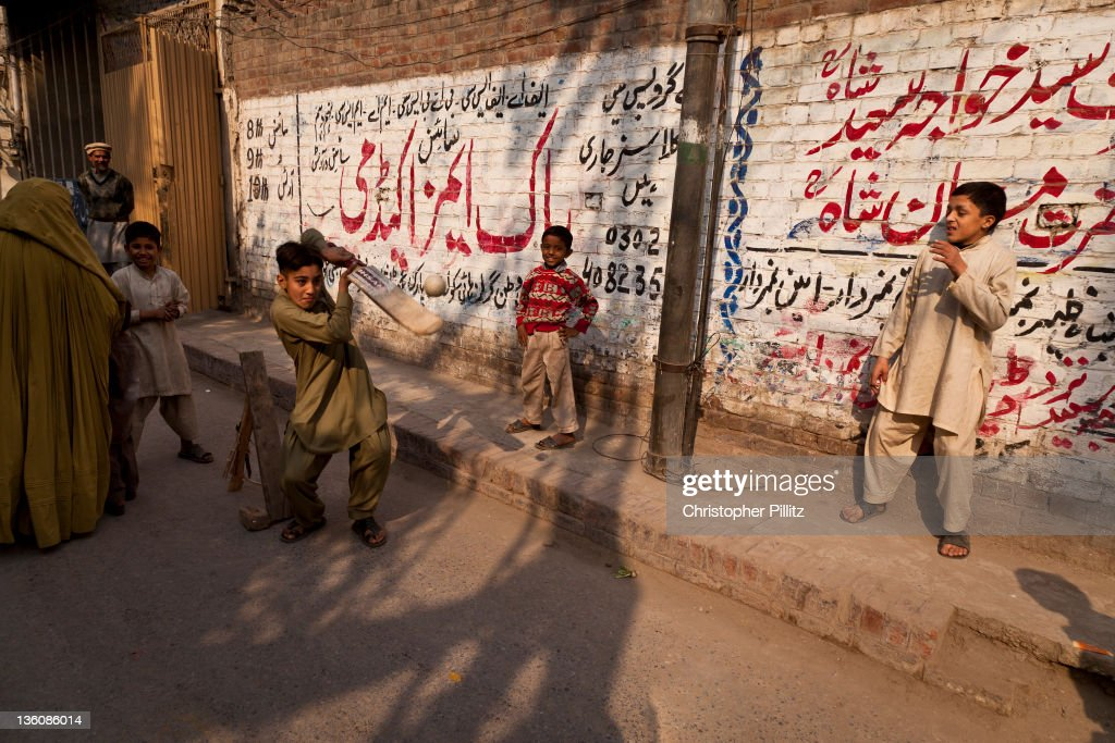 A group of boys playing cricket on a street in Lahore, Pakistan, 15th December 2010.