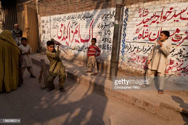 A group of boys playing cricket on a street in Lahore Pakistan 15th December 2010