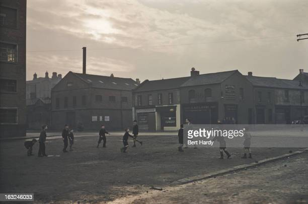 A group of boys playing football in a Belfast street Northern Ireland June 1955 Original publication Picture Post 7825 Belfast pub 25th June 1955