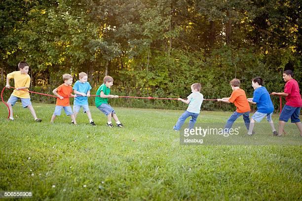 Group of Boys Playing Tug of War Outside