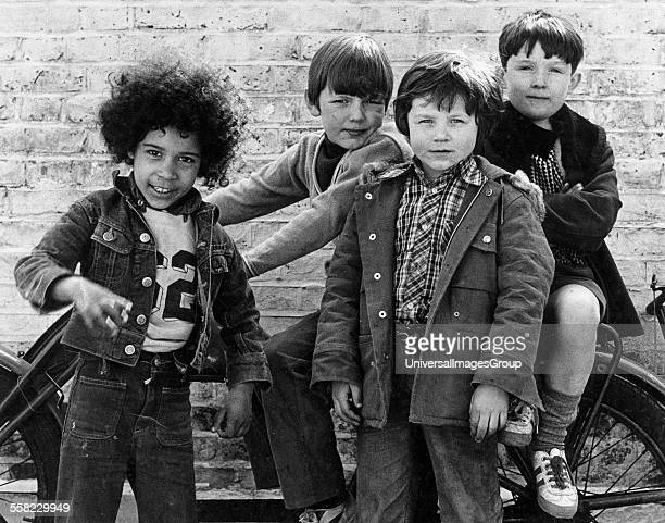 Group of boys posing by a motor cycle, West London, UK, 1973.
