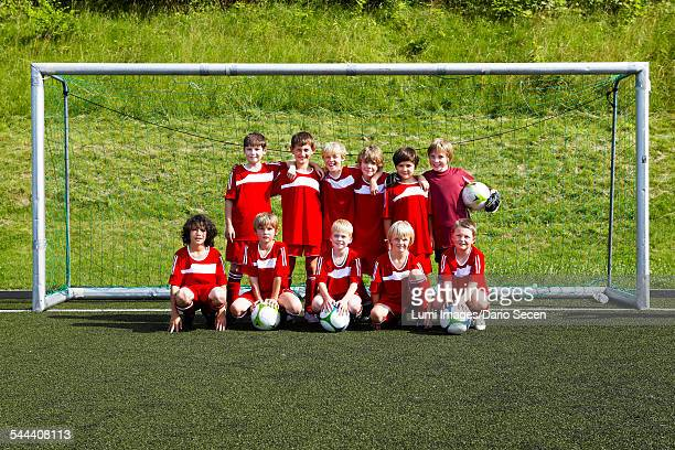 group of boys posing in front of soccer goal, munich, bavaria, germany - équipe de football photos et images de collection