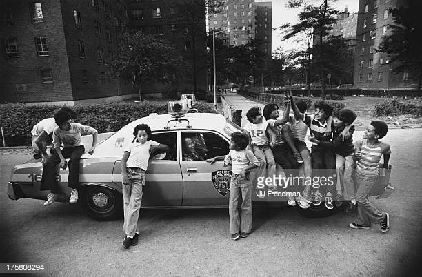 A group of boys sit on a police patrol car in Alphabet City New York City 1980